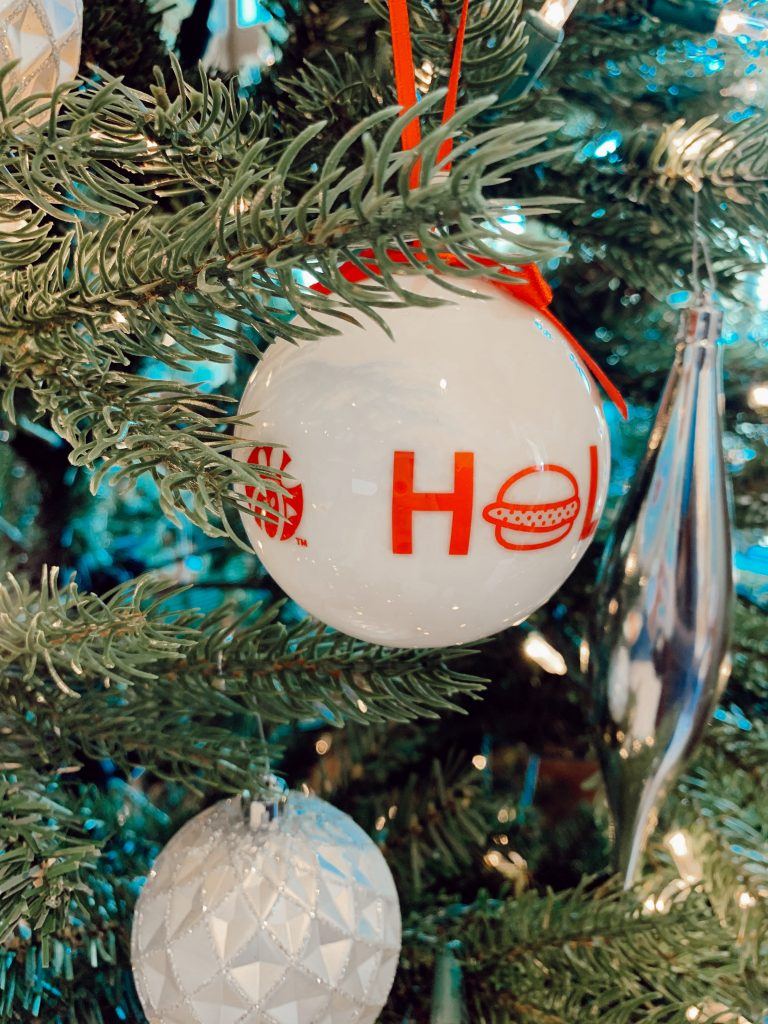 The limited edition 2020 Chick-fil-A ornament is hanging in a Christmas tree that has white Christmas lights and other holiday ornaments.