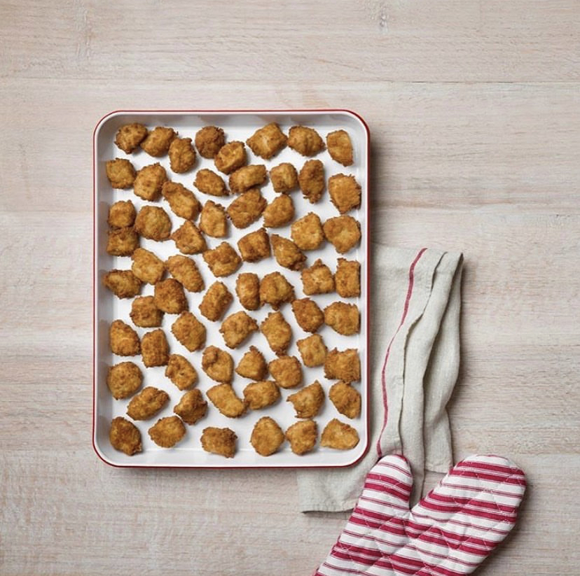 Reheatable nugget order on baking tray with kitchen towel on counter top