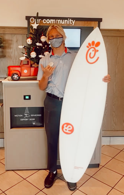 "A team member is holding the RS Surfboard being raffled with a ""shaka"" hand signal."